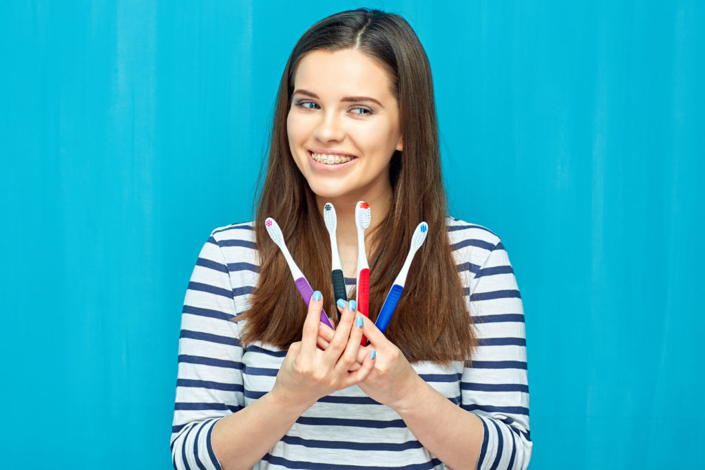Smiling young woman with toothbrushes
